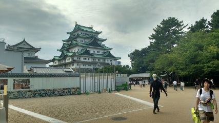 Background: Nagoya Castle. Foreground: a woman is silently followed by a ninja?